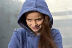 Teenage girl seeks revenge. Smirking teenage girl with blue hoodie thinks about revenge Royalty Free Stock Photo