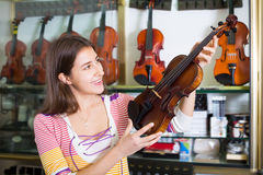 Teenage girl selecting classical violin Stock Photos