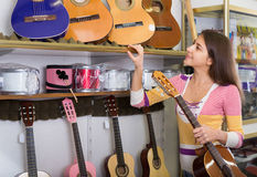 Teenage girl selecting guitar in shop Stock Image