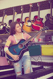 Teenage girl selecting guitar in shop Royalty Free Stock Photos