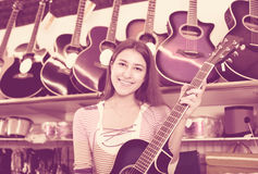 Teenage girl selecting guitar in shop Stock Photography