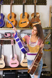 Teenage girl selecting guitar in shop Stock Photos