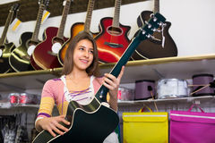 Teenage girl selecting guitar in shop Stock Images
