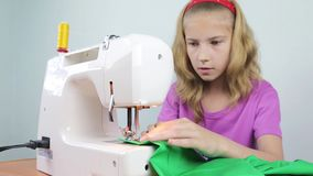 A teenage girl sews braid to the edge of a piece of cloth stock footage