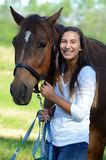 A teen girl laughs with her horse. A teenage girl shares a laugh with her brown horse while standing out in a field Stock Photography