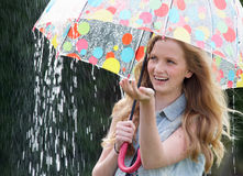 Teenage Girl Sheltering From Rain Beneath Umbrella. Smiling Royalty Free Stock Photography