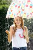 Teenage Girl Sheltering From Rain Beneath Umbrella. Smiling Royalty Free Stock Photos