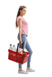Teenage girl with a shopping basket waiting in line Stock Images