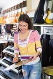 Teenage girl shopping drum kit in music  studio Stock Images