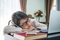 Teenage girl short hair sleep on desk after working. On laptop while sit near window at home office Stock Image