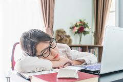 Teenage girl short hair sleep on desk after working. On laptop while sit near window at home office Stock Photos