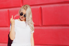 Teenage girl showing middle finger gesture. Rebel and crazy teen hipster in white t-shirt showing rude sign Royalty Free Stock Photography