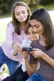 Teenage girl showing mobile phone to siblings Royalty Free Stock Image