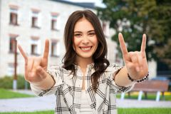 Teenage girl showing rock sign over campus stock image
