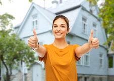 Teenage girl showing thumbs up over house royalty free stock photo
