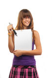 Teenage girl shows on blank piece of paper Royalty Free Stock Image