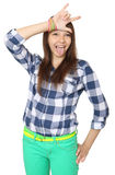 Teenage girl shows tongue and makes hand horns. Mint-colored pants and a plaid shirt. One person, teenager, female, caucasian appearance, isolated image on a Stock Image