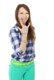 Teenage girl shows tongue and makes hand horns. Mint-colored pants and a plaid shirt. Two identical belts in complimentary colours Royalty Free Stock Photography