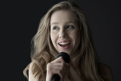 Teenage Girl Singing Into Microphone Royalty Free Stock Photography