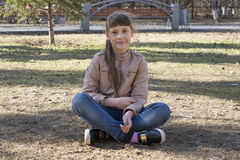 The teenage girl sits on the earth in the park. Royalty Free Stock Photography