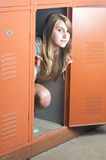 Teenage girl sits in a locker. Being silly Stock Images