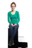 Teenage girl sits on piano in green shirt Royalty Free Stock Images