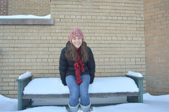 Teenage Girl Sits on a Snow Covered Bench Royalty Free Stock Image