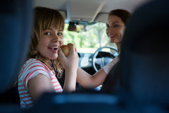 Teenage girl sitting in the back seat while woman driving a car. Happy teenage girl sitting in the back seat while women driving a car Stock Photos