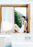 Teenage girl sitting on bathroom window Royalty Free Stock Images