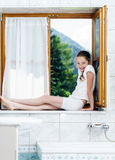 Teenage girl sitting on bathroom window Royalty Free Stock Image