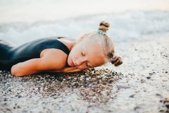 A teenage girl is sitting on the beach in a black swimsuit. A teenage girl is sitting on the beach on the tide line in a black swimsuit Royalty Free Stock Photography