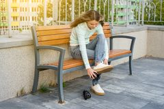 Teenage girl sitting on a bench in the city dresses wheels on sneakers Royalty Free Stock Image