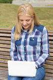 Teenage girl sitting on bench in park with laptop Royalty Free Stock Photos