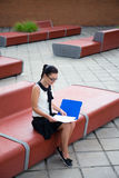 Teenage girl sitting on bench and reading something Royalty Free Stock Photography