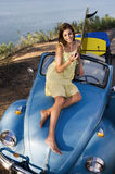 Teenage girl (17-19) sitting on car bonnet, listening to MP3 player, smiling, elevated view Royalty Free Stock Photos