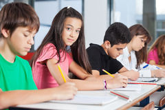 Teenage Girl Sitting With Classmates Writing At Stock Photos