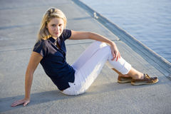 Teenage girl sitting on dock by water Stock Images
