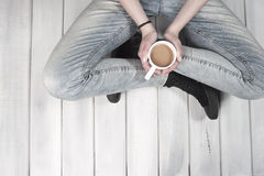 Teenage girl sitting on floor holding a cup of coffee Royalty Free Stock Photography