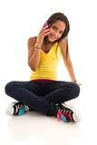 Teenage girl sitting on floor talking on cellphone Royalty Free Stock Photos