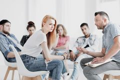 Teenage girl during therapy. Teenage girl sitting in front of psychologist during group therapy royalty free stock image