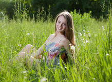 Teenage girl sitting in the grass Stock Photo