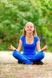 Teenage girl sitting in lotus Royalty Free Stock Image