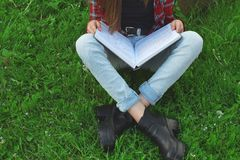 Teenage girl sitting in meadow stock photography