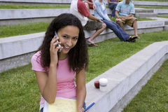Teenage girl (17-19) sitting near friends, study notes in lap, using mobile phone, smiling Royalty Free Stock Photos