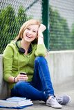 Teenage girl sitting outdoors Stock Image