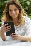 Teenage Girl Sitting Outdoors With E-Book Royalty Free Stock Photography