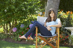 Teenage Girl Sitting Outdoors In Garden Chair Stock Photo
