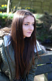 Teenage girl sitting on a park bench on a cold day Royalty Free Stock Images