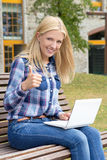 Teenage girl sitting in park with laptop and thumbs up Royalty Free Stock Photography