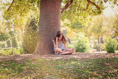 Teenage girl is sitting and relaxing under a big tree Stock Photos